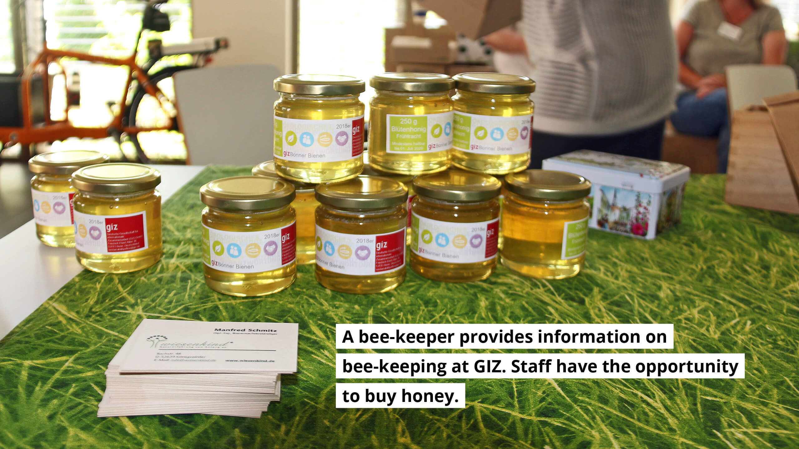 A bee-keeper provides information on bee-keeping at GIZ. Staff have the opportunity to buy honey.